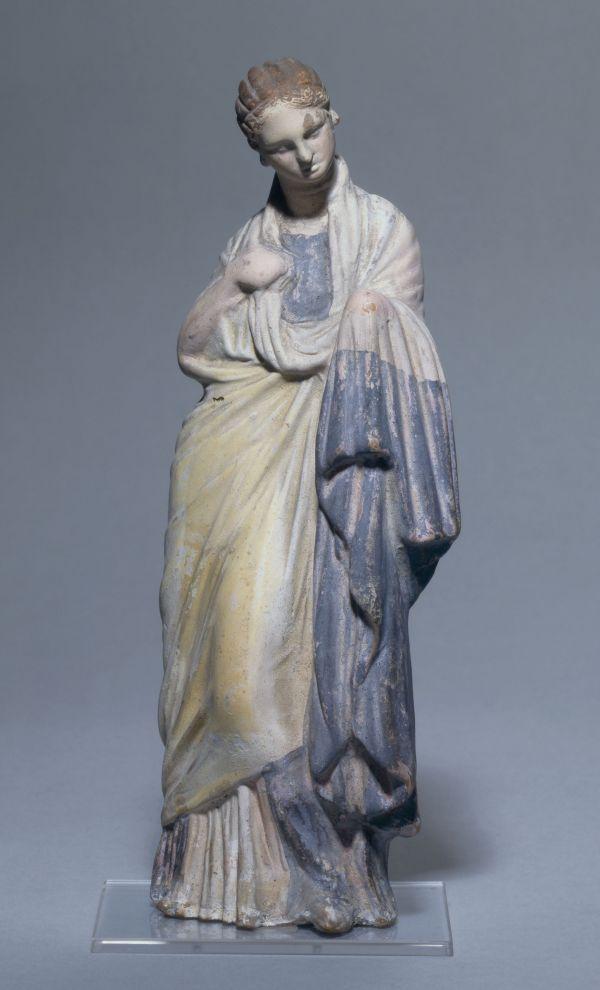 Bild Die Terrakotte aus Attika zeigt eine junge Frau im safranfarbenen Mantel mit breitem Purpursaum, 300–275 v. Chr.